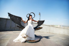 Bride on bronze bench with wings Royalty Free Stock Photography