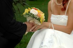 Bride and broom holding hands. A close up of a bride and groom holding hands together and their bridal bouquet Royalty Free Stock Photo
