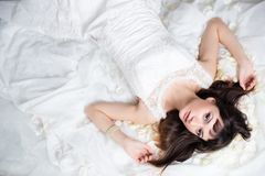 Bride with brunette hair lying over white. High angle view Royalty Free Stock Images