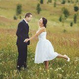 Bride burst of laughing. Young bride burst of laughing. Wedding couple in field Royalty Free Stock Images