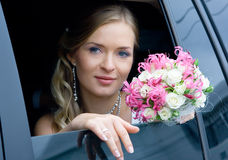 Bride in the car. Serenity bride with flower bouquet siting in the car. Shallow DOF, focus on flowers royalty free stock images