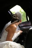 Bride in car. The bride looks in a window of the automobile stock images