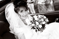 Bride in the car. Smiling young bride with bouquet in the car Stock Image