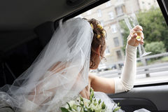 Bride in car. The bride looks in a window of the automobile royalty free stock photo