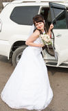 Bride and the car. Bride with bouquet at the open car door Stock Image