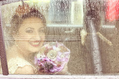 Bride in the car on a rainy day Royalty Free Stock Photography