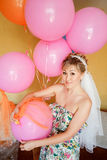 Bride in casual clothes with veil among pink balloons, preparing for wedding. Stock Photography