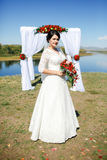 Bride during ceremony outdoors with bouquet on river, arch of roses and white cloth. Royalty Free Stock Photos
