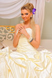 The bride  with champagne in the uriant inteior. Stock Photo