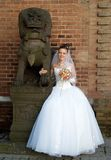 Bride and chinese lion. Bride with wedding  bouquet of flowers and chinese guardian lion statue Royalty Free Stock Images