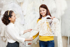 Bride chooses bridal clothes at shop of wedding fashion Royalty Free Stock Photo