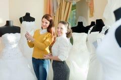 Bride chooses bridal outfit at wedding store Royalty Free Stock Photos