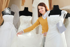 Bride chooses wedding gown at bridal boutique. Smiling pretty bride chooses wedding gown at bridal boutique stock photography