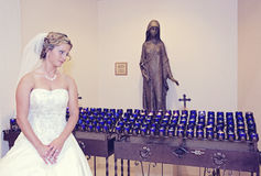 Bride in a church. Bride looking at votive candles in catholic church Stock Photos