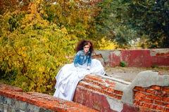 Bride in city park. Beautiful bride in wedding dress and denim jacket in autumn park Stock Photo