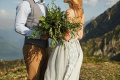 the bride closed her eyes and whispers something to her fiance, close-up, green bouquet on the background of mountains stock photo