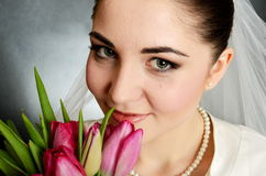 Bride closeup portrait. Beautiful, young bride closeup portrait. Young female holding flowers near her face Stock Photo