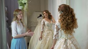 Bride at the clothes shop for wedding dresses she is choosing a dress and the designer is assisting her