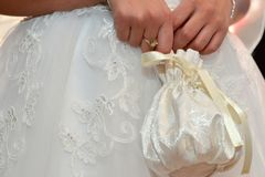 Bride clothing details. Wedding ceremony acessories. Bride dress, hands and bag details Stock Images
