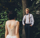Bride comes to the groom. On the lawn in the forest royalty free stock photo