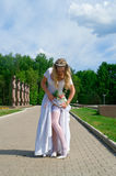 Bride corrects a stocking. Bride in a white wedding dress corrects a stocking in park Stock Photography