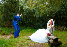 Bride cought a groom for her with a fishing rod, Royalty Free Stock Photos