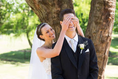 Bride covering eyes of groom in garden Royalty Free Stock Photo