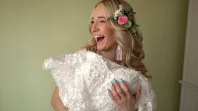 The bride covers herself with a dress, and laughs. Blonde, hair decorated with flowers stock footage