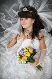 Bride with a curly hair and a wedding bouquet from yellow roses Royalty Free Stock Image