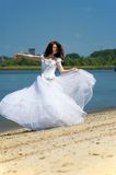 Bride dances on a beach. Bride on a sandy beach turns round itself Stock Images