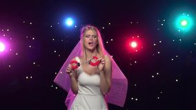 Bride dancing with gift at bachelorette party. Slow motion. Happy bride dancing with gift at bachelorette party, black background and stroboscope lamps provide stock footage