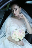 Bride with dark hair in luxurious wedding dress with  bouquet of flowers sitting in car Royalty Free Stock Image