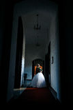 The bride in a dark large corridor stands at the window in her w Stock Image