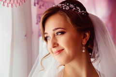 Bride with delicate face traits stands thoughtful. Before the window Royalty Free Stock Photography