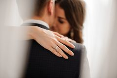 Bride demonstrates her elegant diamond engagement ring. Handsome bride brunette demonstrates her elegant diamond engagement ring on the bride`s shoulder on a royalty free stock image