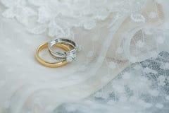 Wedding bands close up on wedding dress fabric stock image