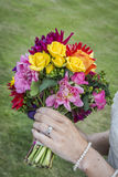 Bride displaying flowers and wedding ring Stock Images