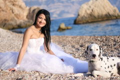 Bride and dog. Portrait of beautiful young bride with dalmatian on the sea coast Royalty Free Stock Photo