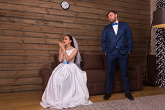Bride doing makeup, evil groom in waiting. Portrait of bride doing makeup and evil groom in waiting, wooden interior of the room on background royalty free stock image