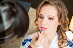 Bride doing makeup in the morning in a room Royalty Free Stock Image