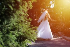 Bride doing pirouette in the park. Bride with white wedding dress doing a pirouette in the park, green alley Stock Photo
