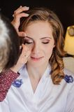 Bride doing wedding make-up in the morning Stock Photography