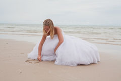 Bride drawing heart on the sand stock photos