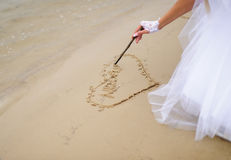 Bride drawing heart on the sand Stock Image