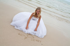 Bride drawing on the sand royalty free stock images