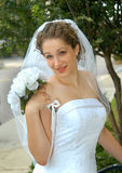 Bride so Dreamy. Bride smiles at camera.  Her bouquet is sitting on her shoulder.  White roses with white ribbon.  She has on a veil and strapless gown Stock Image
