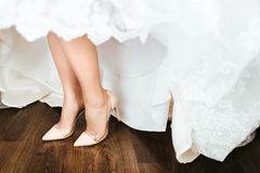 Bride in a dress and beige shoes is standing on a wooden floor. Close-up Royalty Free Stock Image