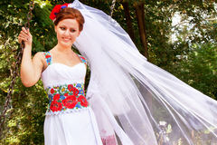 Bride in the dress and the bridal veil in the ukrainian style. Beautiful caucasian bride in the dress and the bridal veil in the ukrainian style is standing on Royalty Free Stock Photography