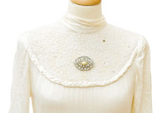 Bride dress detail - genuine 1930. Genuine 1930 white satin bride dress. Jewellery vintage brooch with diamonds. Detail on the lace. Isolated over white Royalty Free Stock Photo