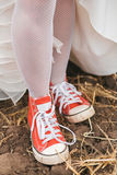 Bride in dress in dirty red plimsolls on ground Royalty Free Stock Photo